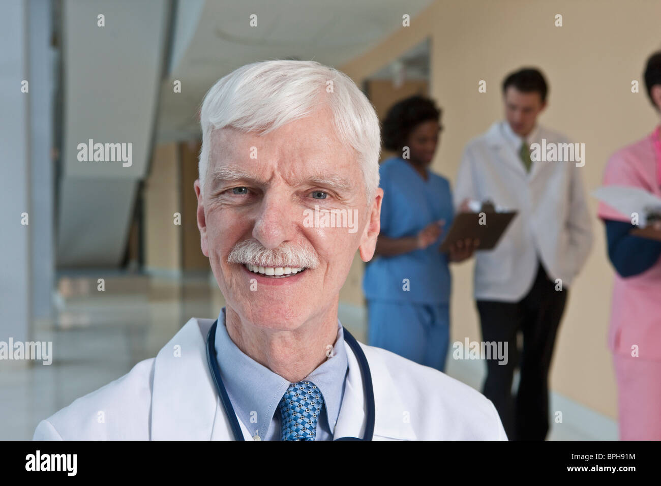 Doctor smiling with his colleagues in the background - Stock Image