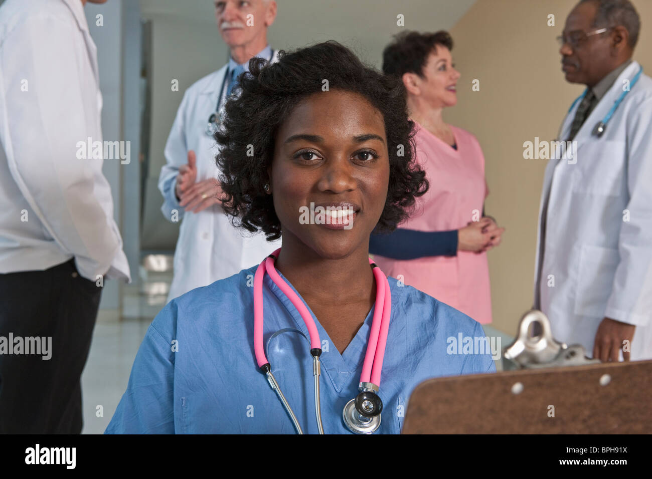 Jamaican female nurse smiling with her colleagues in the background - Stock Image