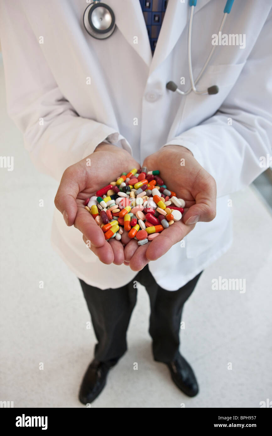 Doctor holding a handful of pills - Stock Image