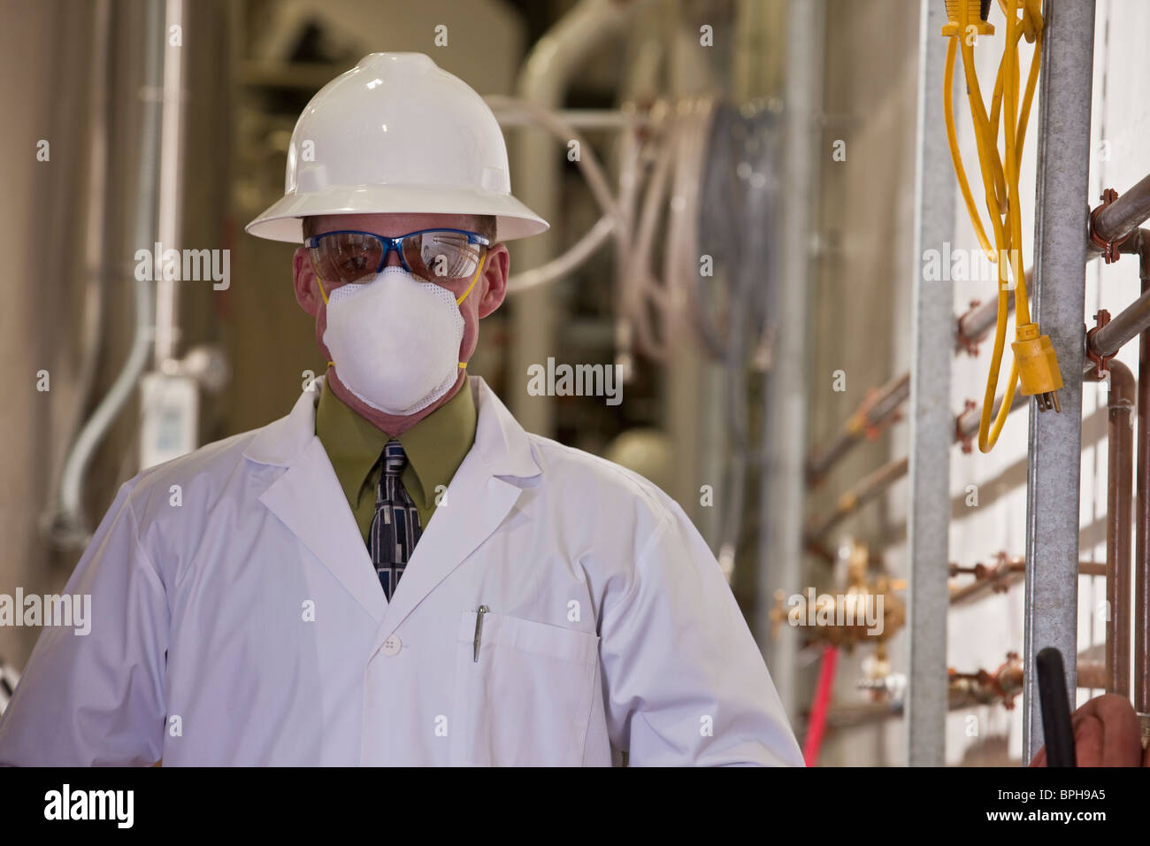 Engineer wearing a pollution mask in a chemical plant - Stock Image