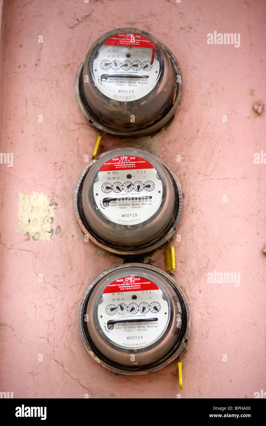 Three electricity meters on a wall  - Stock Image