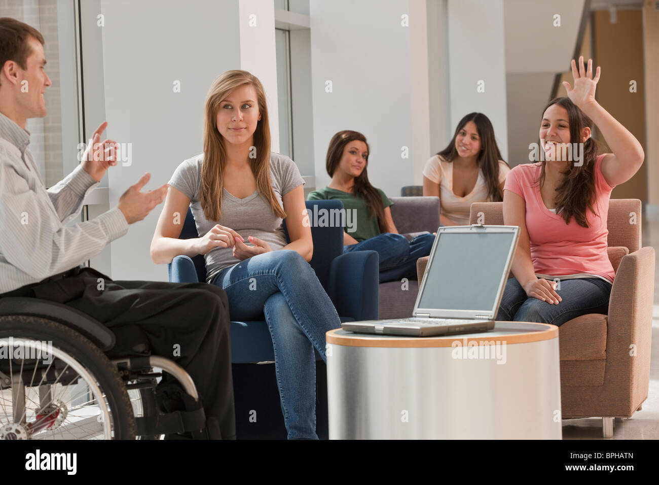 Teacher with spinal cord injury giving a lecture to students in classroom - Stock Image