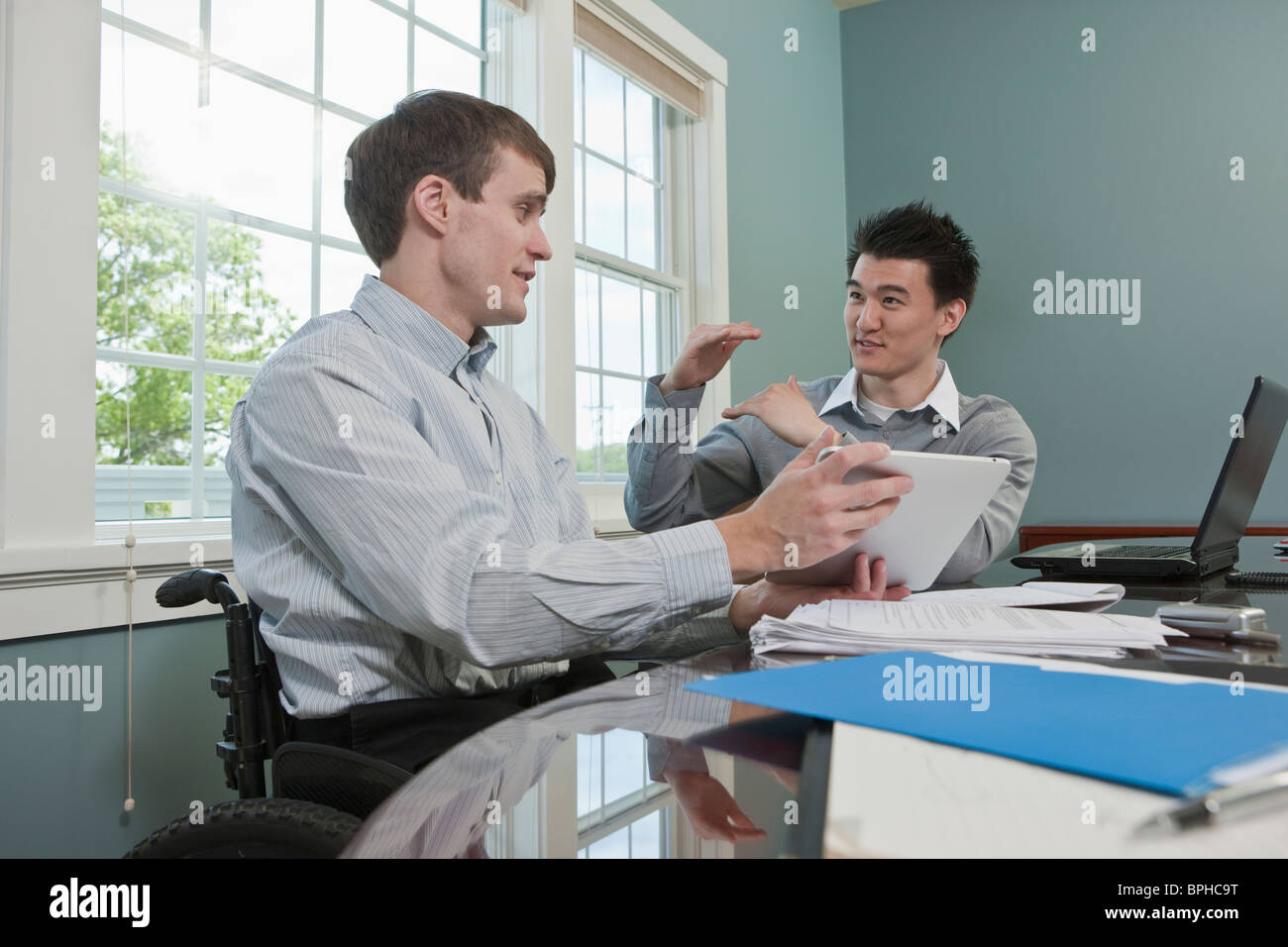 Businessman with spinal cord injury discussing with his colleague in an office - Stock Image