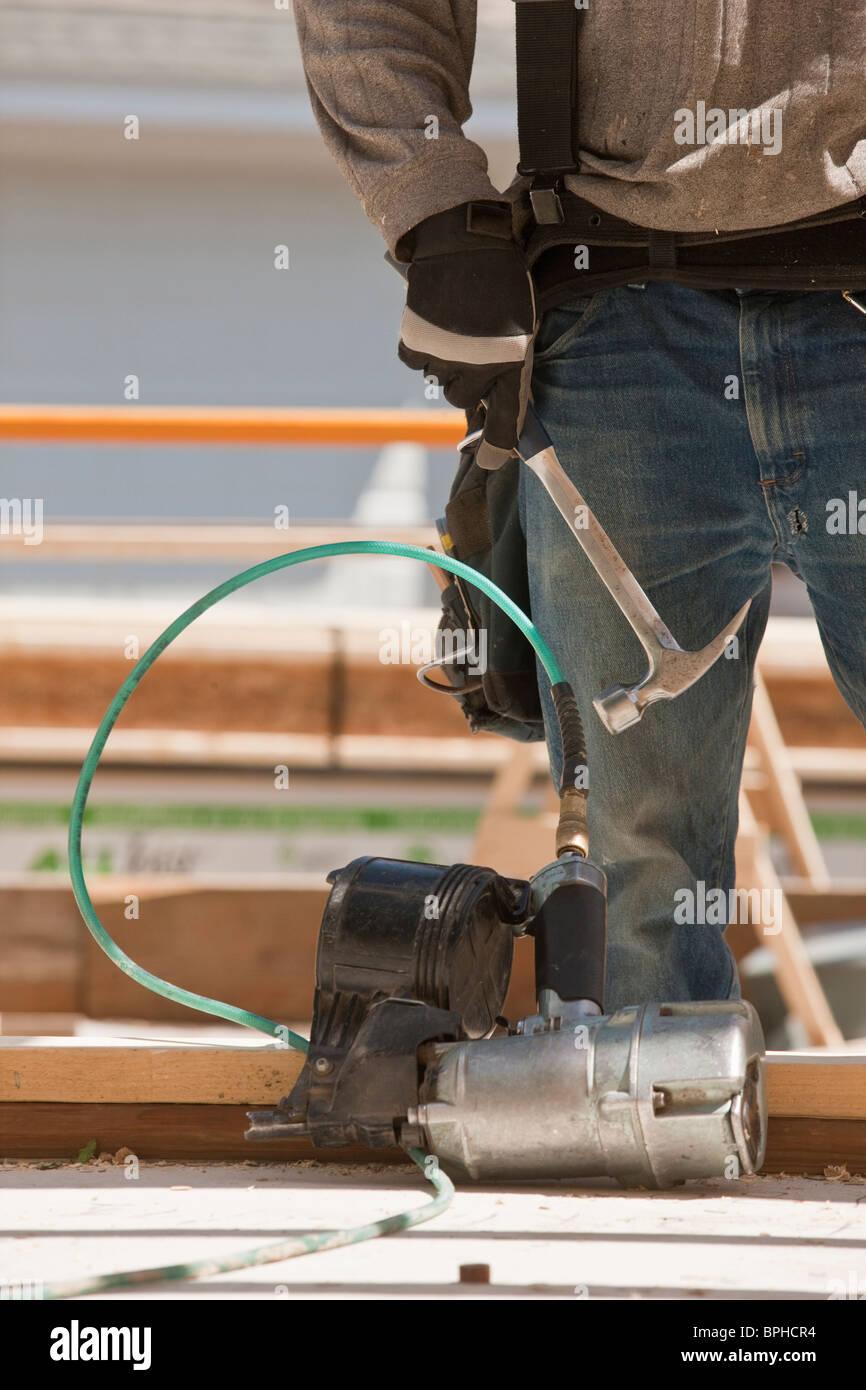 Carpenter and nail gun at a construction site - Stock Image