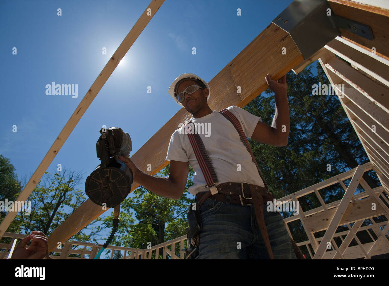 Carpenter using a nail gun at a construction site Stock Photo