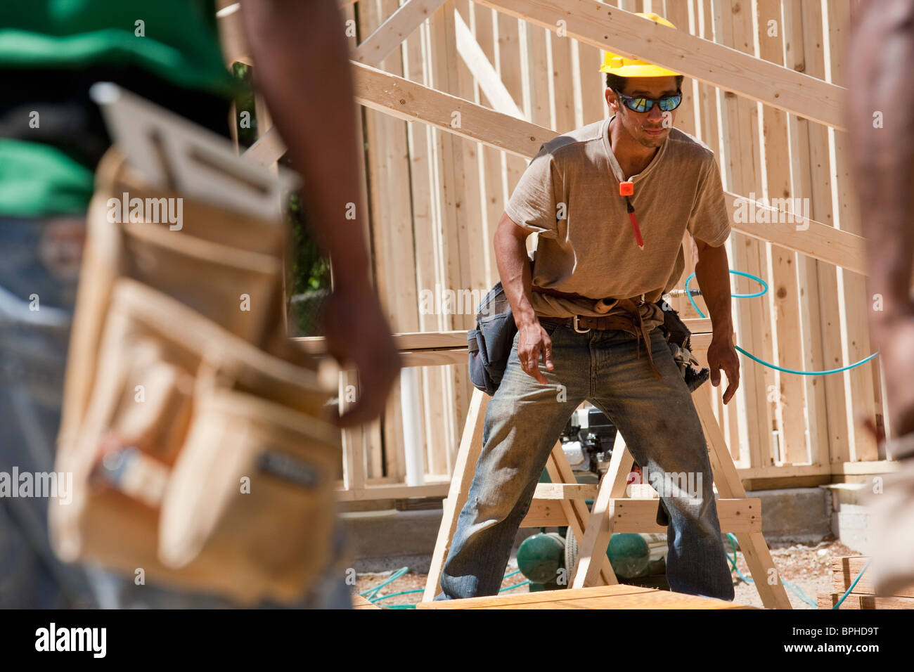Carpenters working on a framed house - Stock Image