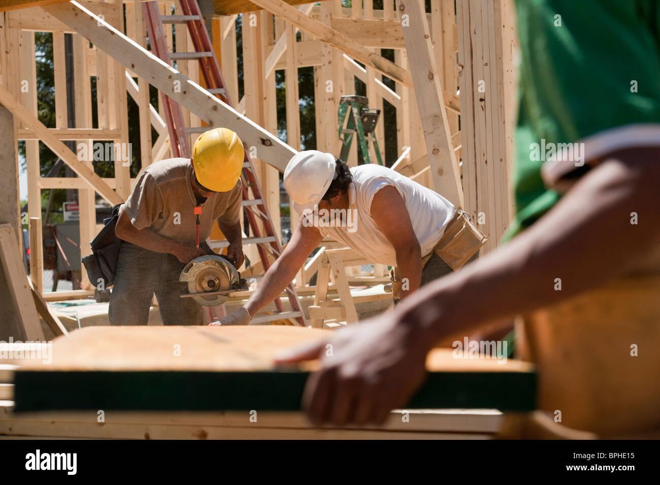Carpenters sawing beam - Stock Image