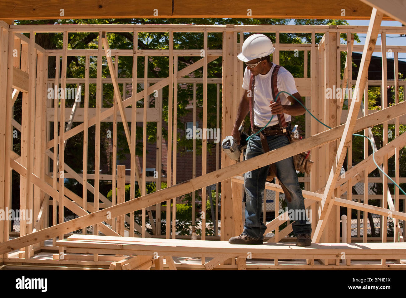 Carpenter standing at a construction site holding a nail gun - Stock Image