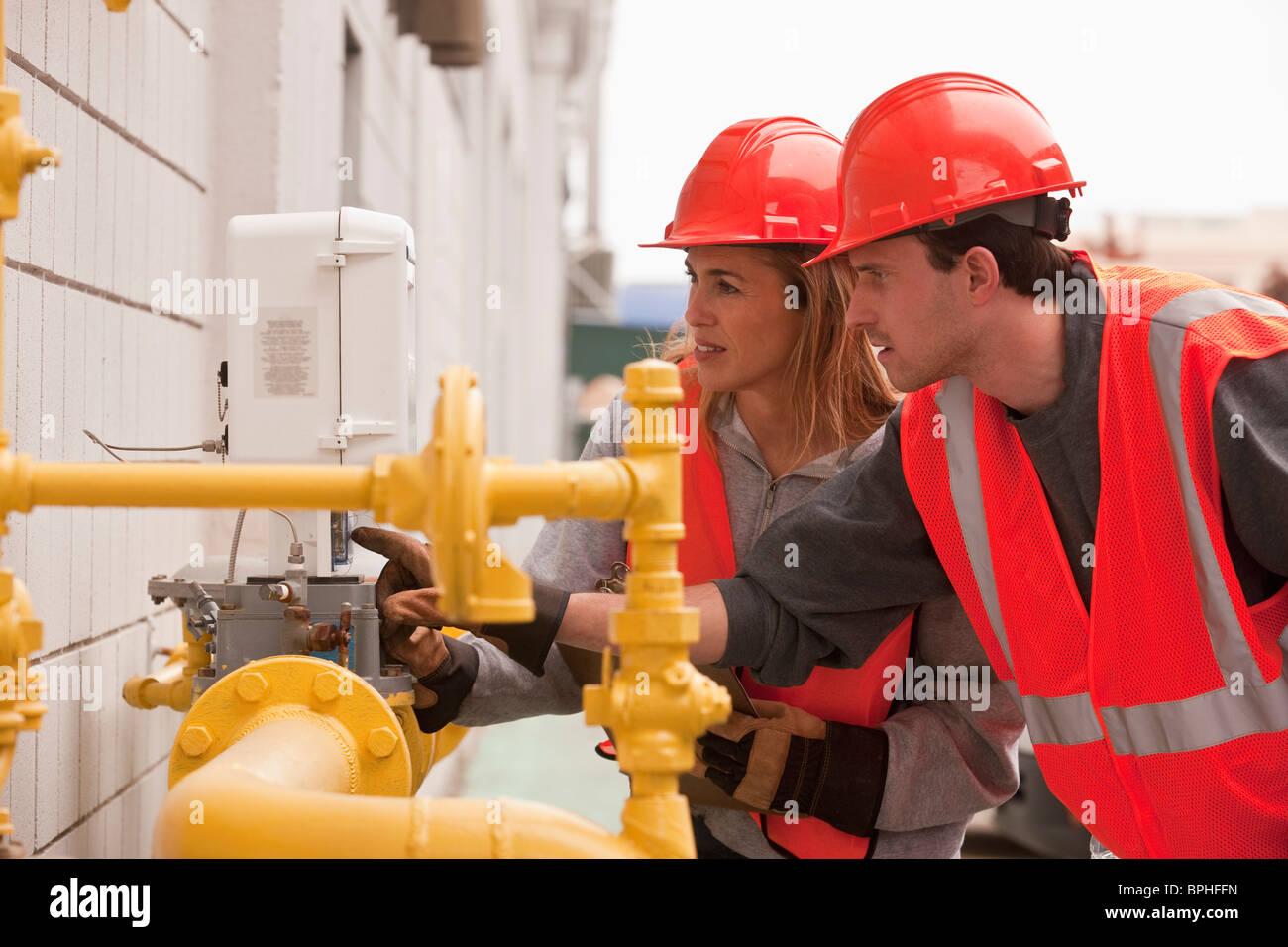 Process engineers taking meter reading near pipeline - Stock Image