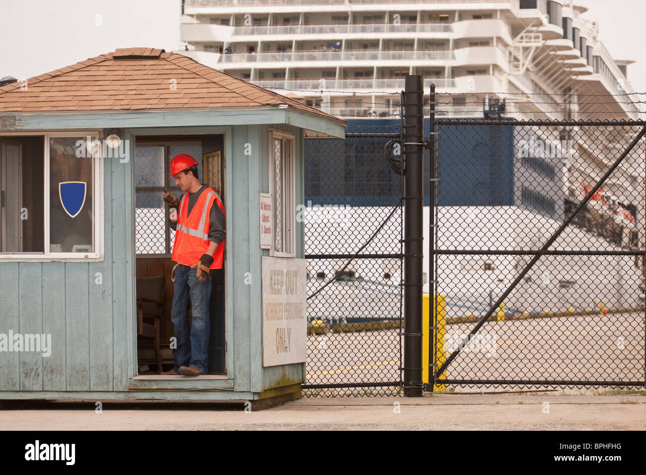 Engineer with a walkie-talkie at security point with a passenger ship in the background - Stock Image