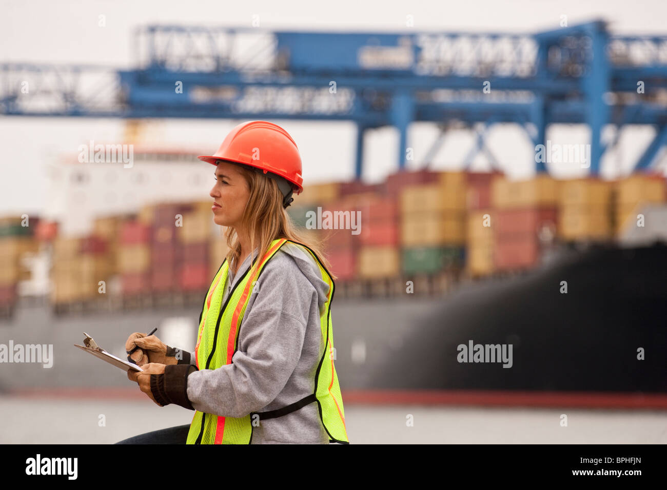 Female transportation engineer working on a commercial dock - Stock Image
