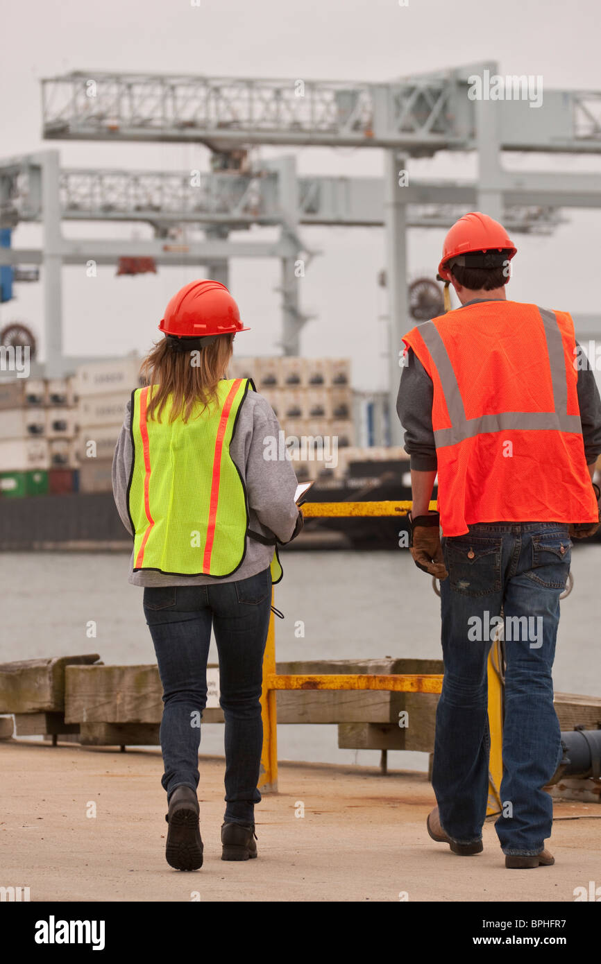Transportation engineers walking towards a container ship - Stock Image