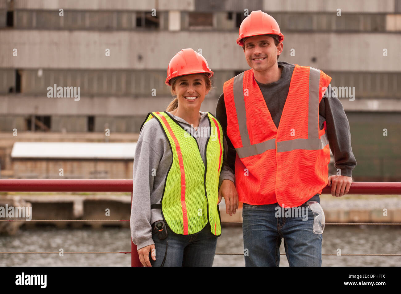 Marine terminal engineers at a commercial dock with an industrial building in the background - Stock Image