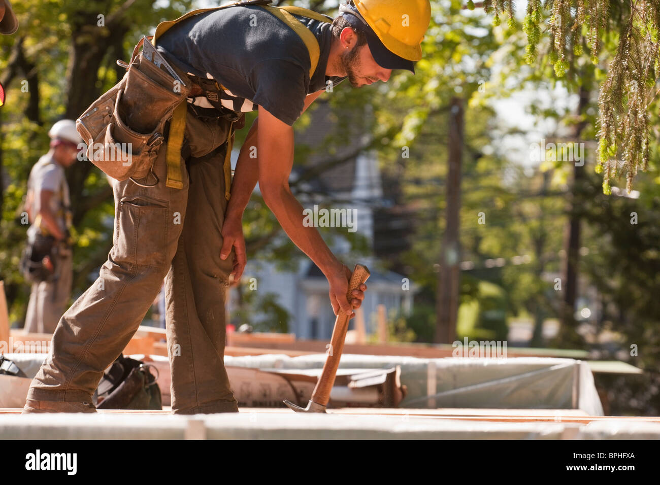 Carpenter using a claw hammer at a construction site - Stock Image