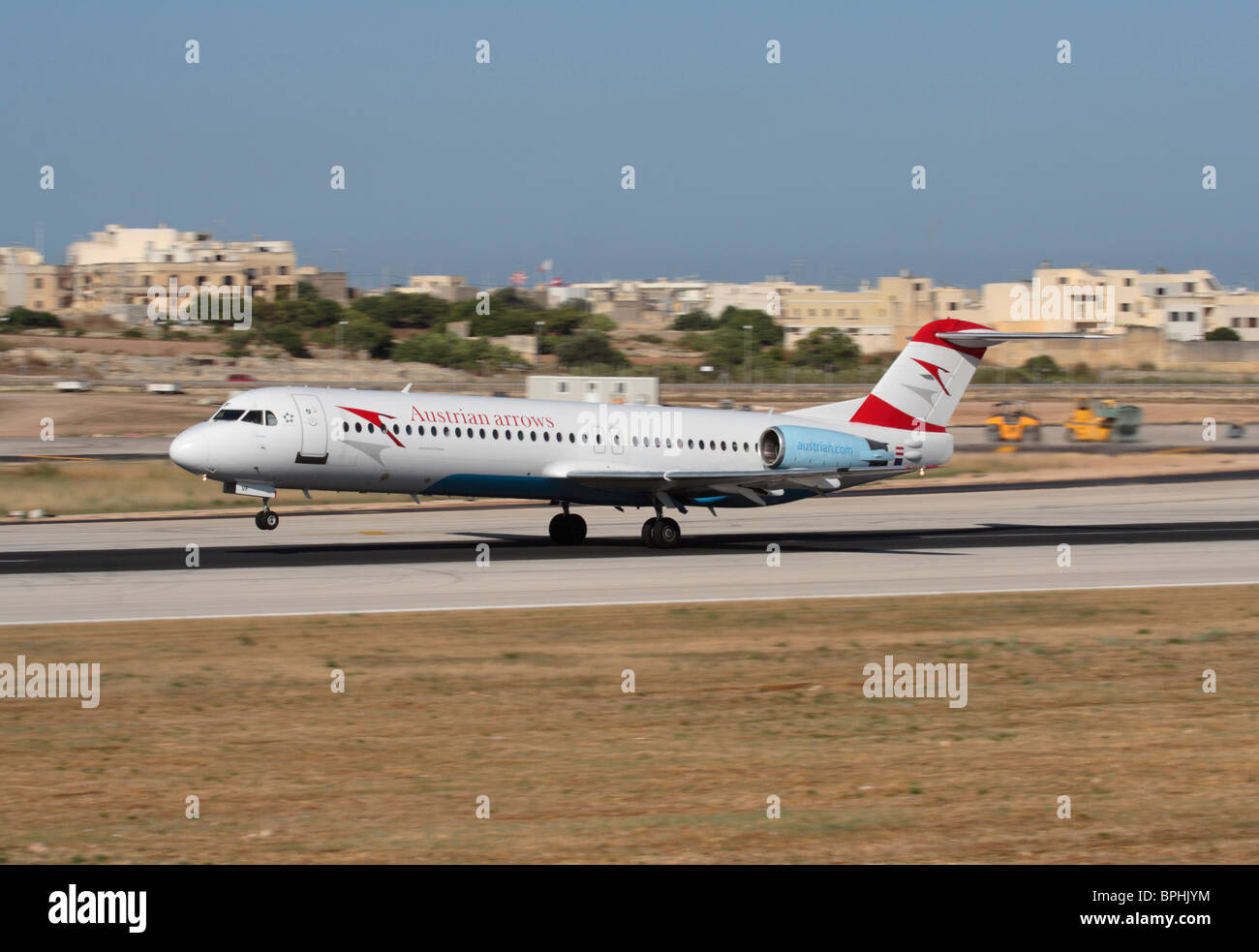 Austrian Arrows Fokker F100 passenger jet plane on the runway at Malta International Airport during takeoff - Stock Image