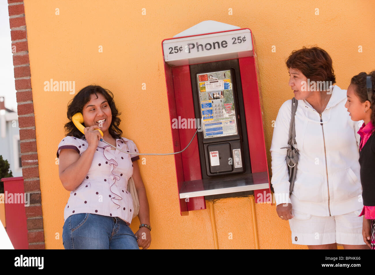 Hispanic woman talking on a pay phone with her family