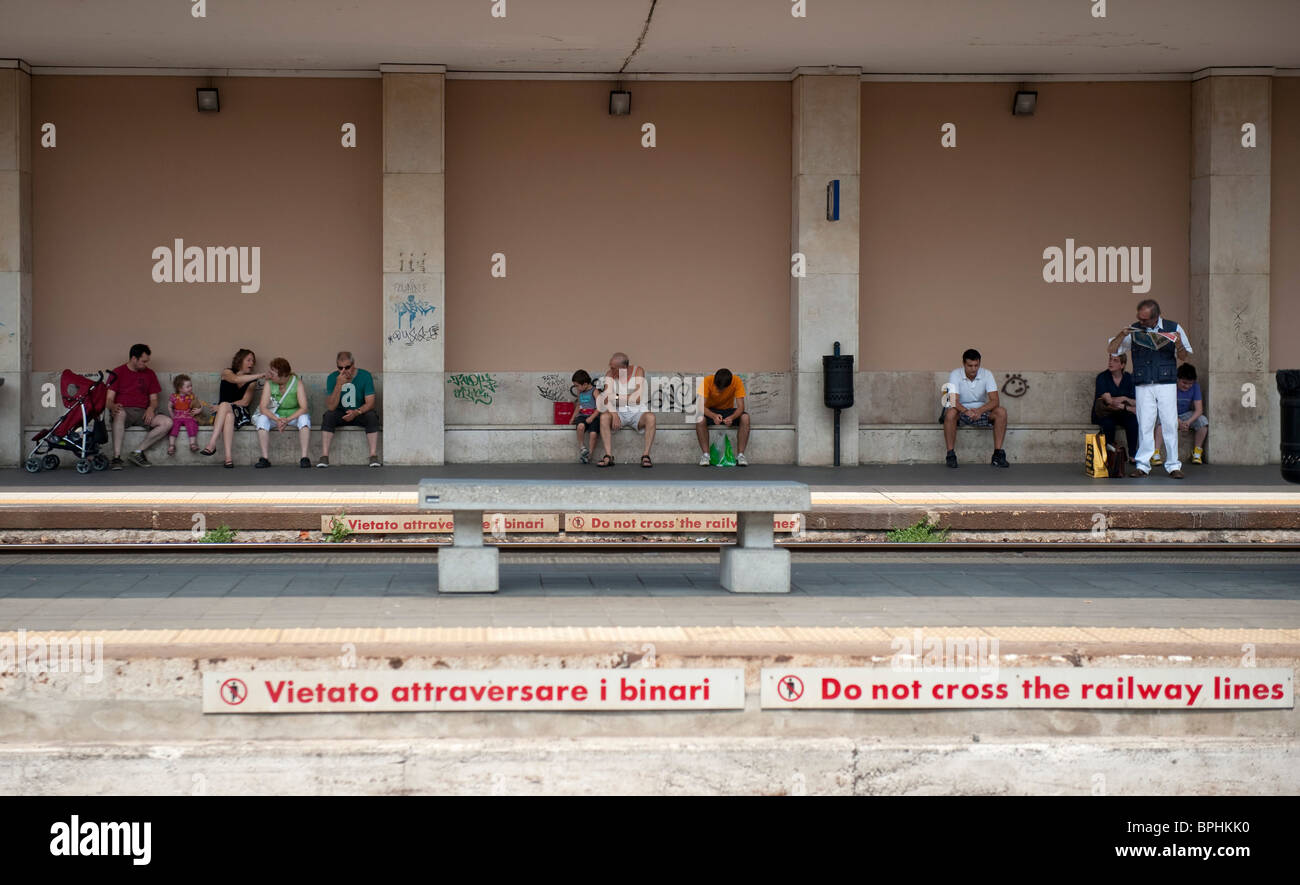 Passengers wait for the train on a hot summer day at railway station Monza Italy - Stock Image