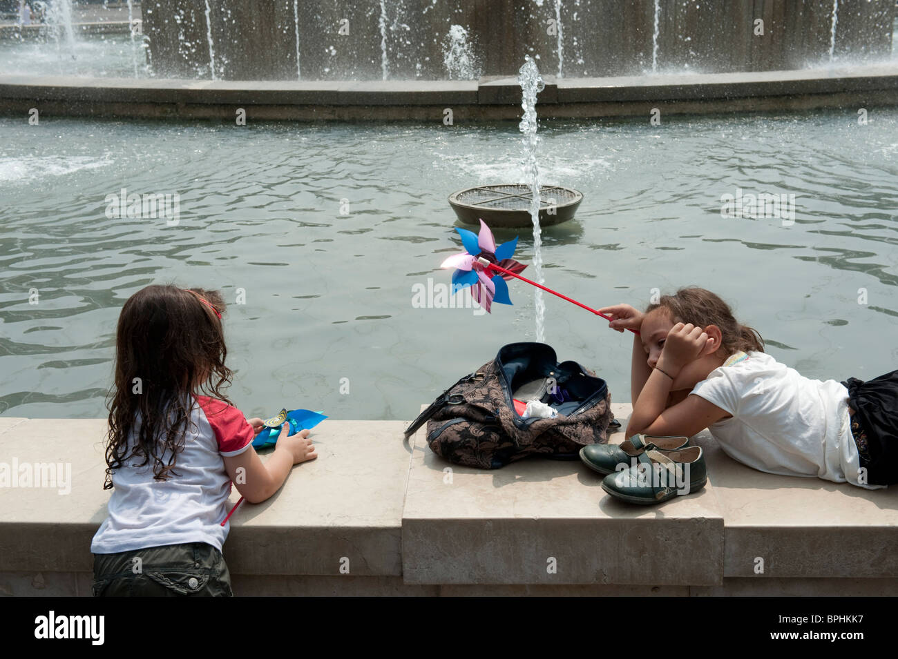 Two girls play on a fountain border in a hot summer day in Milan Italy - Stock Image