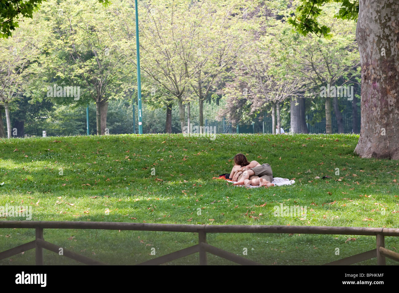 a couple sunbathing in a city parkon a hot summer day in Milan Italy - Stock Image