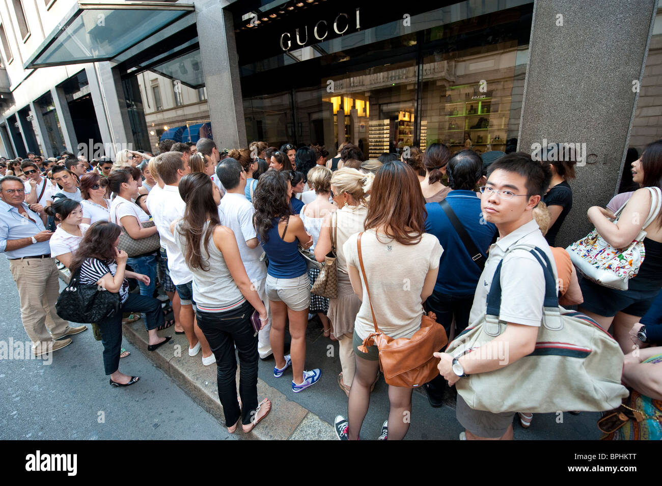 Long queue for the summer sales outside the  Gucci store via Montenapoleone Milan Italy - Stock Image