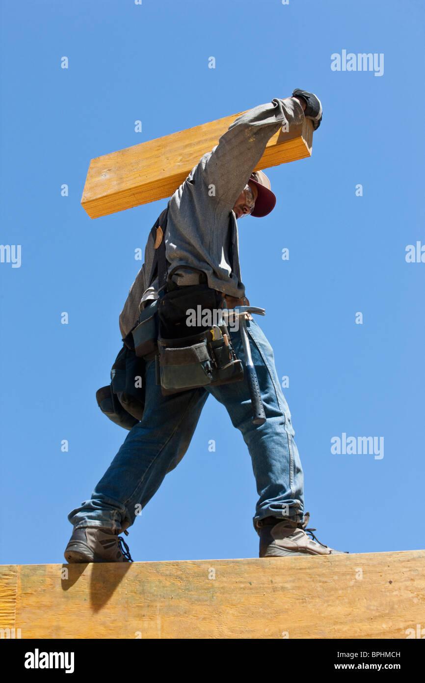 Carpenter carrying beam - Stock Image