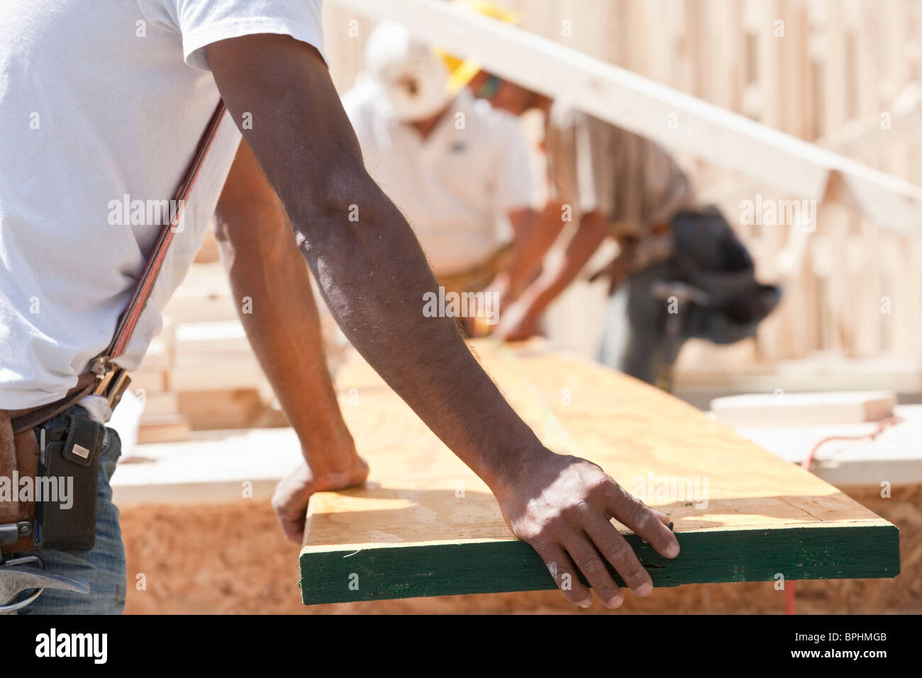 Carpenters holding a plank at a construction site Stock Photo