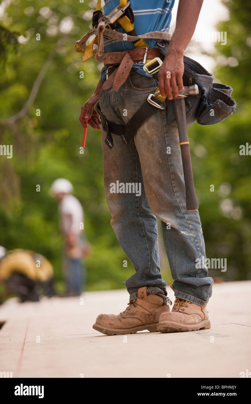 Carpenter working at a construction site - Stock Image