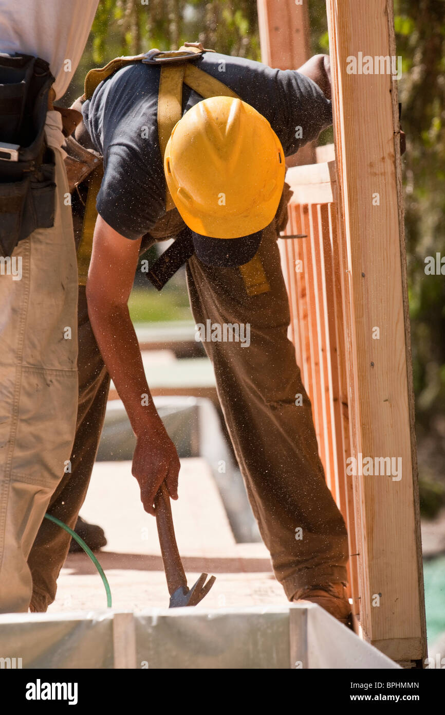 Carpenters using claw hammer at a construction site - Stock Image