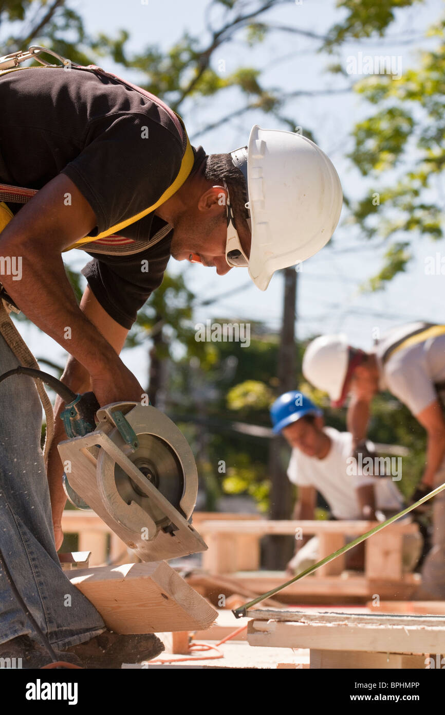 Carpenters using circular saw at a construction site with gable frame in the background - Stock Image