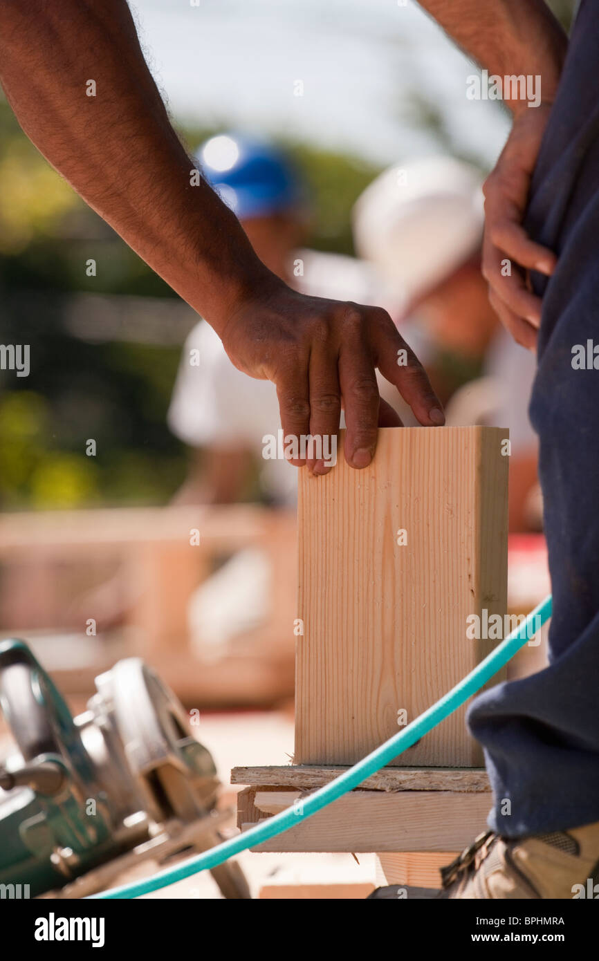 Carpenters positioning wood trim at a construction site Stock Photo