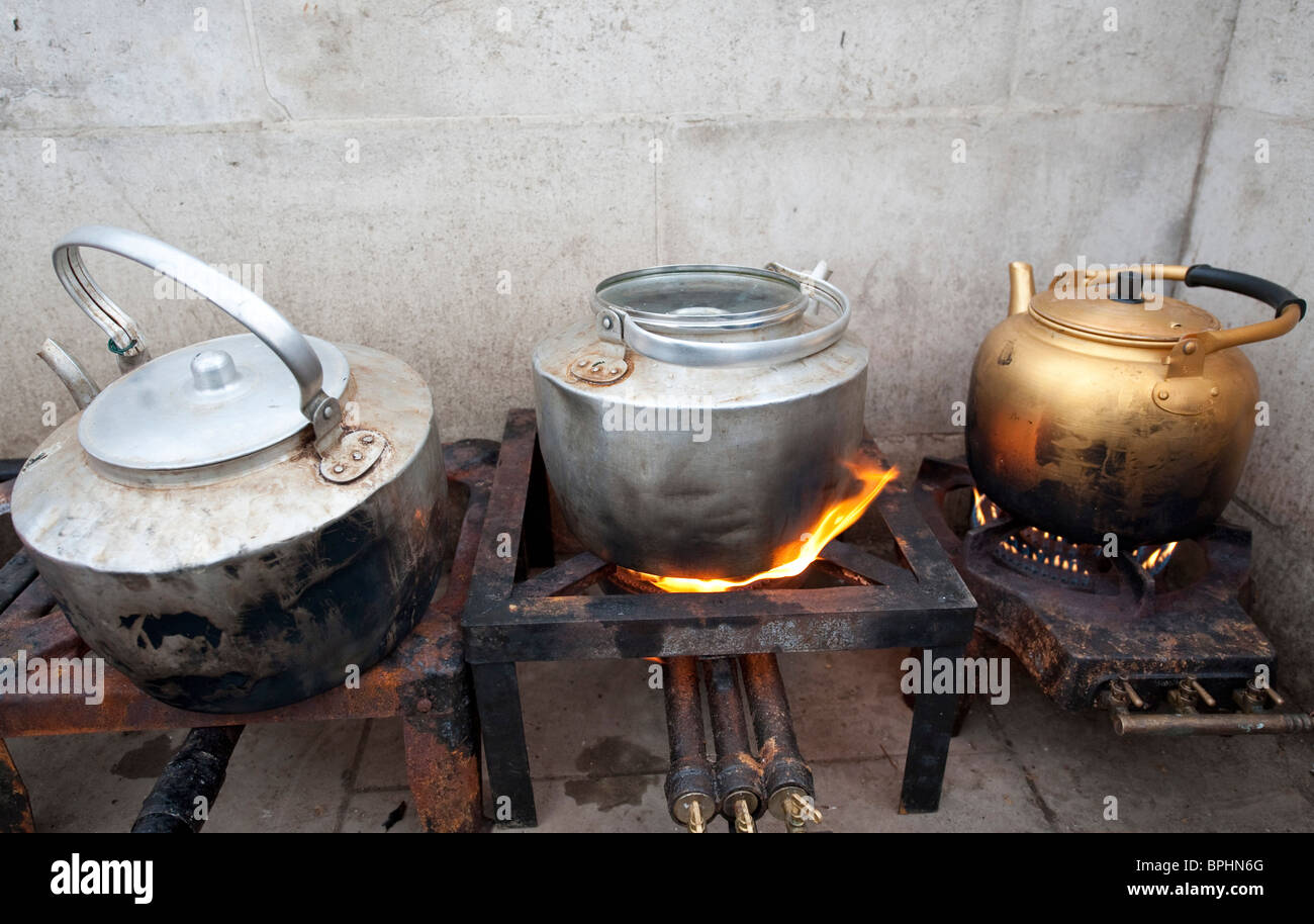 Old fashioned kettles on gas stove - Stock Image