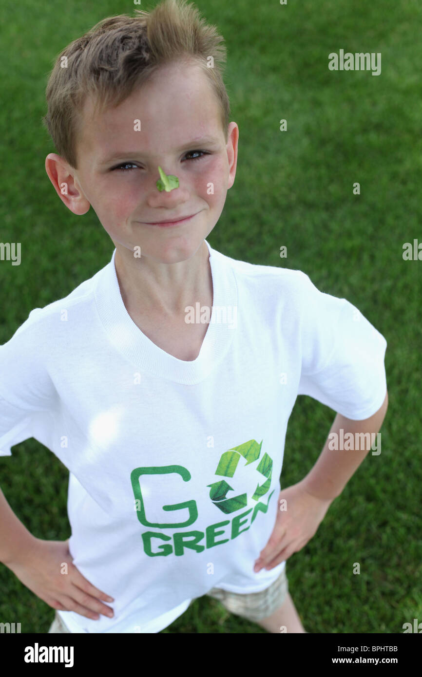 smiling young boy standing  & wearing with 'go green 'tee shirt - Stock Image