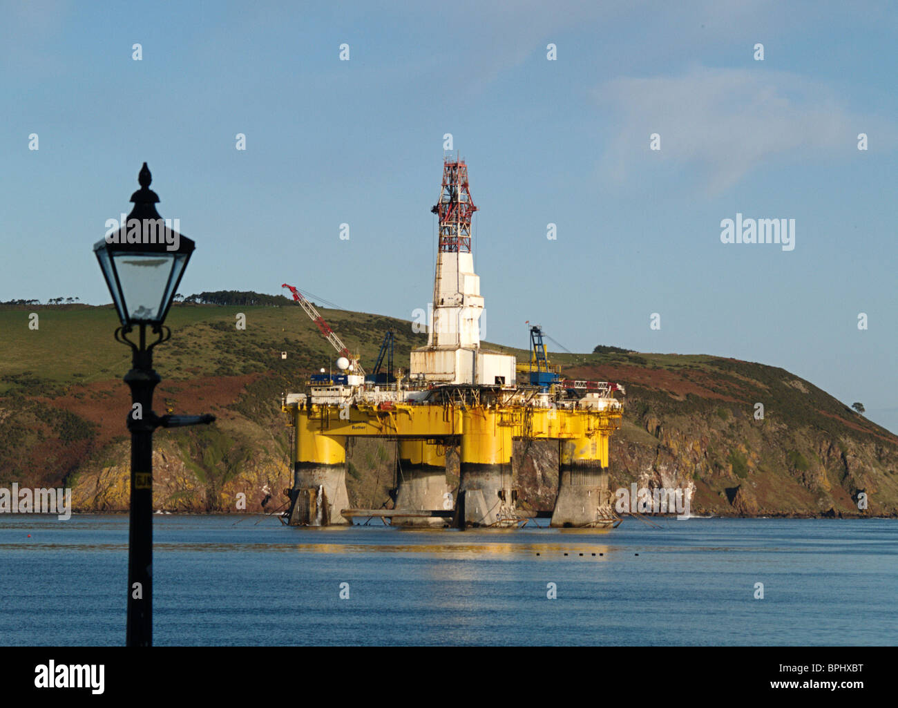 The semi-submersible Oil Drilling rig Transocean Rather moored in the Cromarty Firth, Scotland, framed by an street lamp Stock Photo