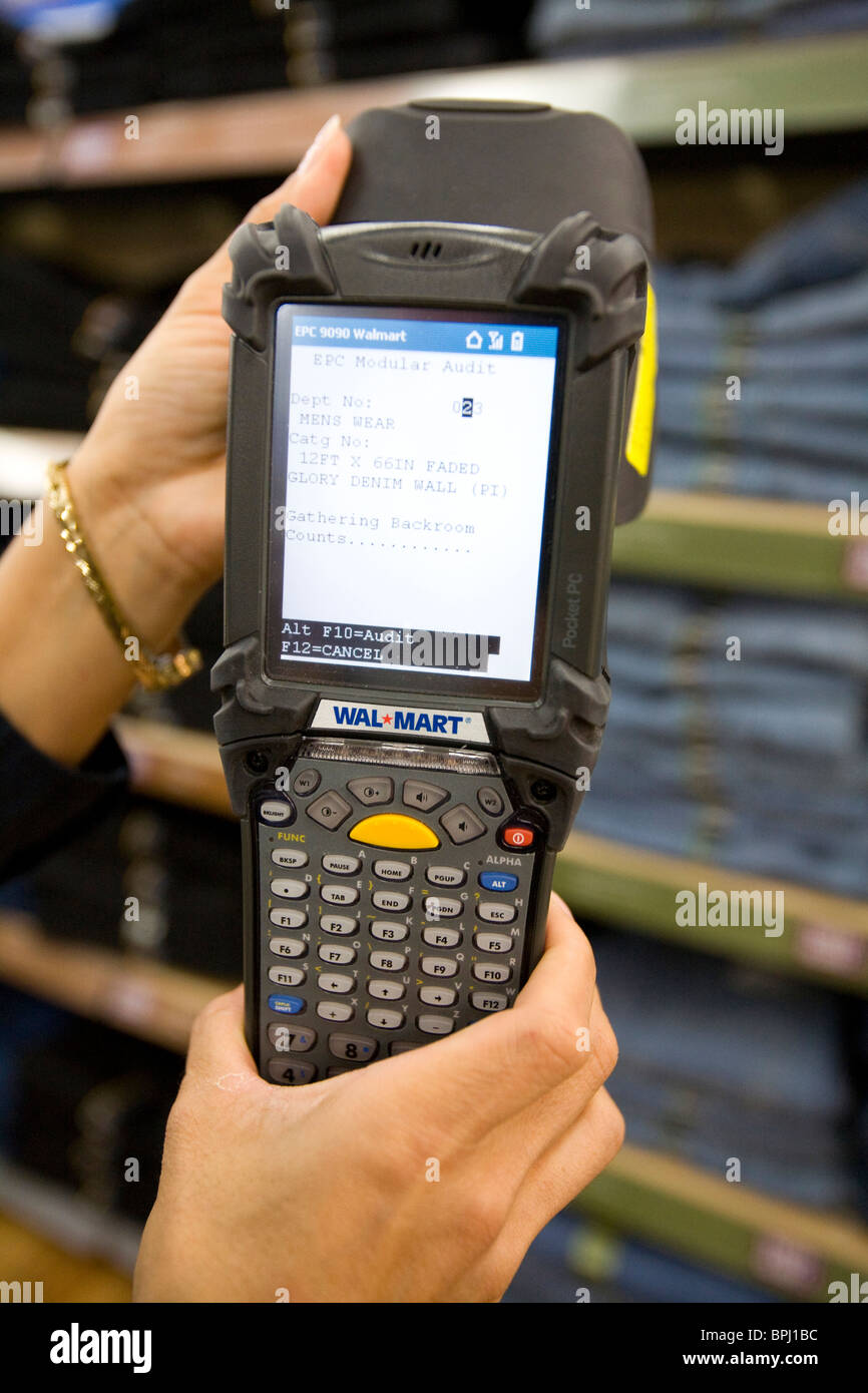 A Sales Associate Uses A Telxon Handheld Scanner To Read