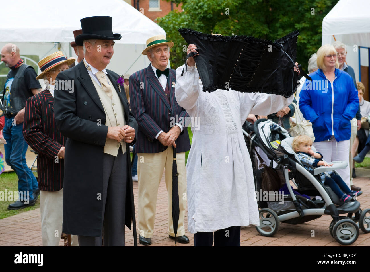 Gentlemen in period costume one holding up a corset at the annual Victorian Festival in Llandrindod Wells Powys - Stock Image