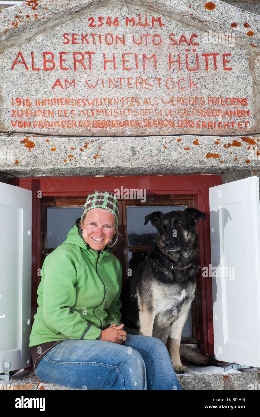 Woman and dog in front of a Albert Heim mountain lodge, Urner Alps, Canton of Uri, Switzerland - Stock Image