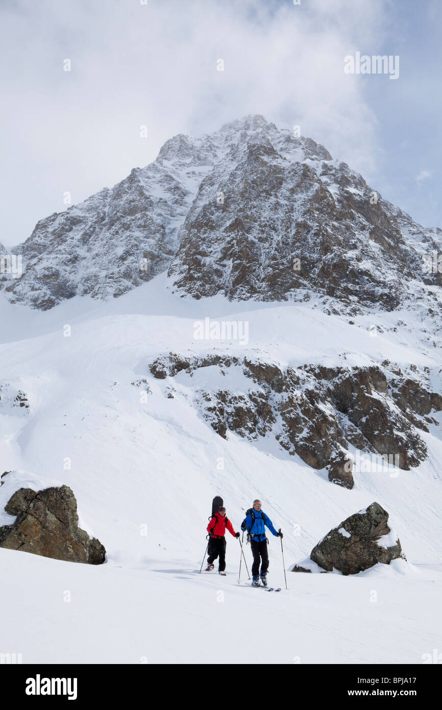 Skier and snowboarder with snowshoes on slope, Puschlav, Grisons, Switzerland - Stock Image