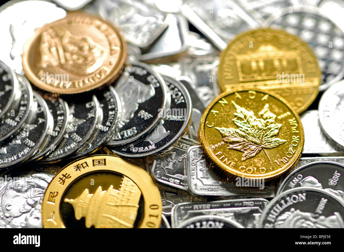 Gold and Silver bullion in small coins: 1g silver rounds and 10th ounce gold coins - Stock Image