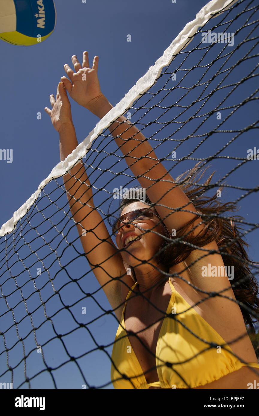 Young woman playing volleyball, wearing a yellow bikini, Mallorca, Balearic Islands, Spain - Stock Image