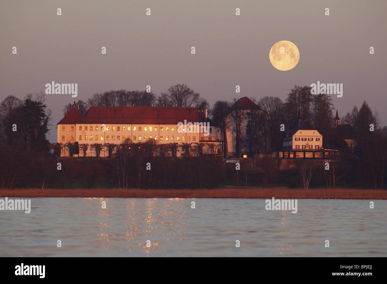Rising moon over the old palace of Herrenchiemsee, Herreninsel, Lake Chiemsee, Chiemgau, Bavaria, Germany - Stock Image