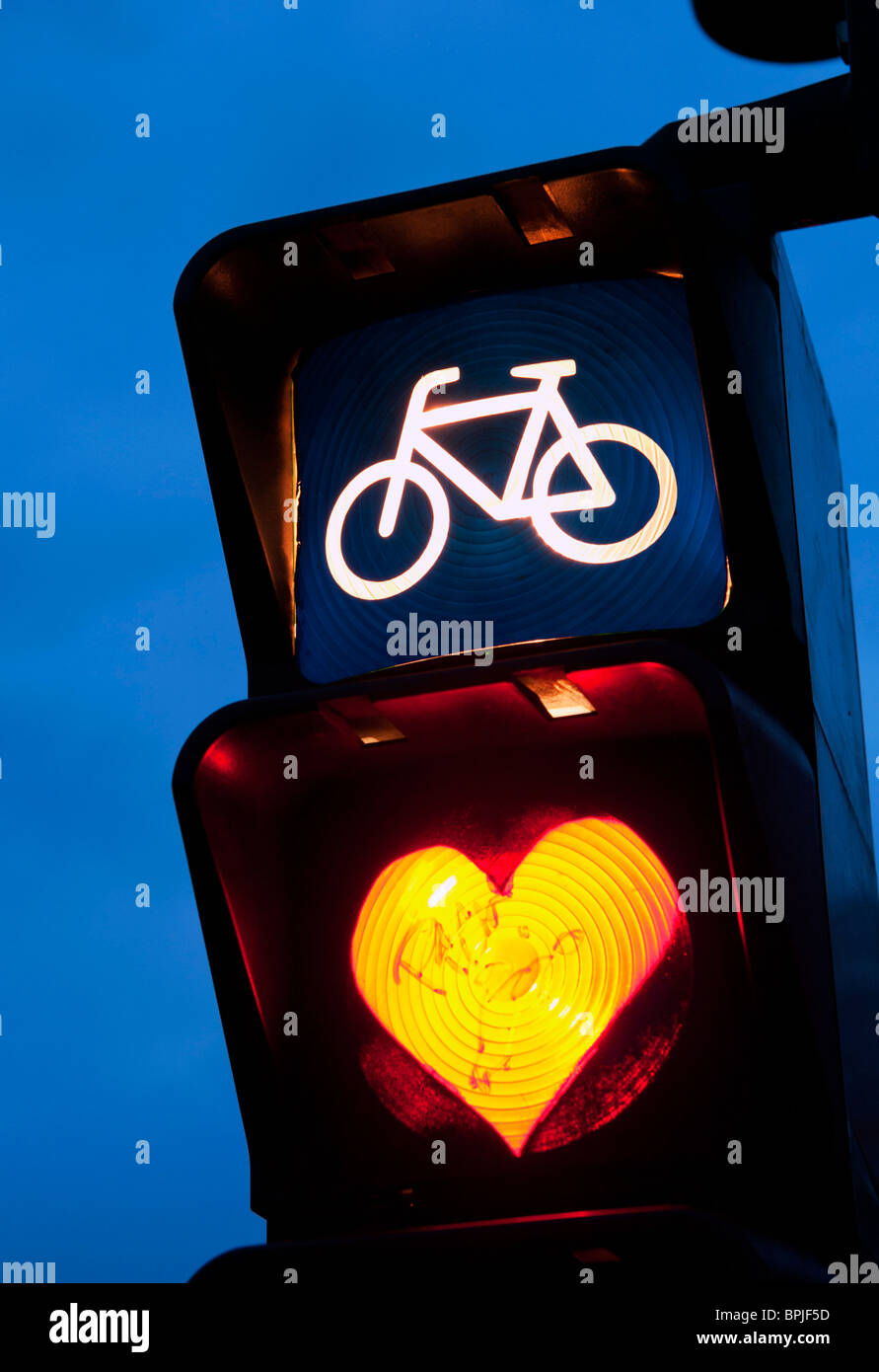 Detail of red cycle traffic stop light painted with love heart in Berlin Germany - Stock Image