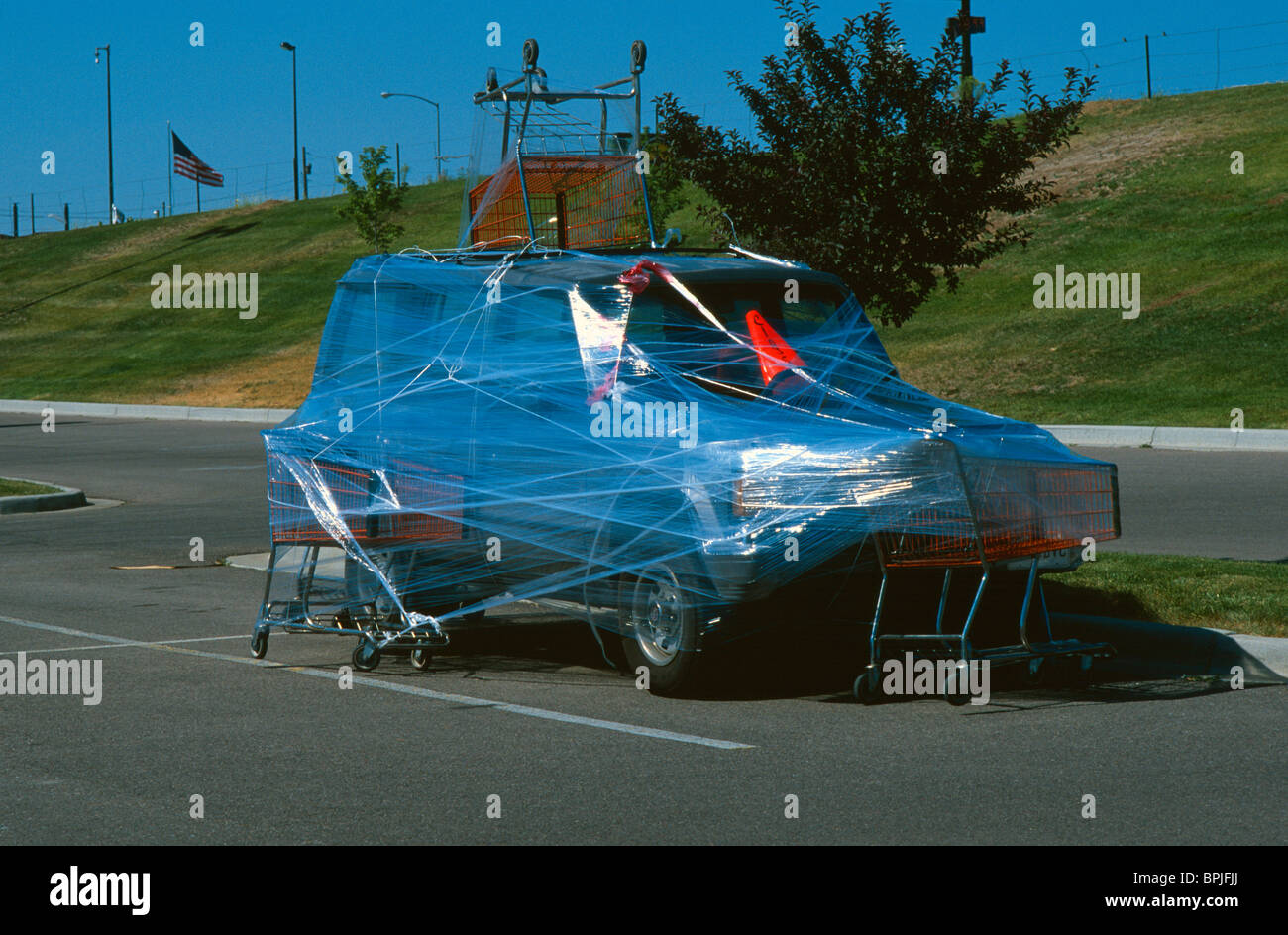 Practical joke. Car in parking lot wrapped with clear plastic. - Stock Image