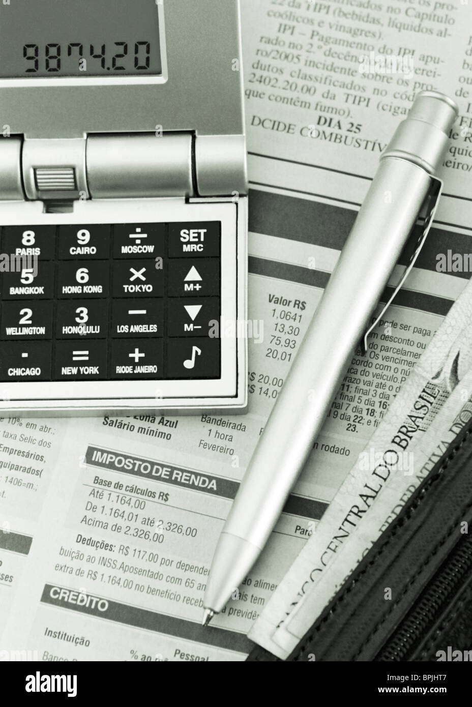 newspaper, calculator with Brazilian Real bank notes, pen, elevated view, close-up - Stock Image