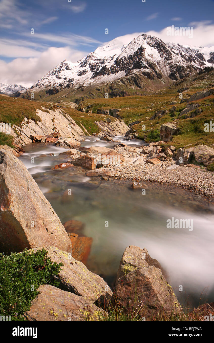 Gavia Pass, Brixia province, Lombardy region, Italy. Gavia torrent at 2.651 meters on the sea. Tresero peak as background - Stock Image