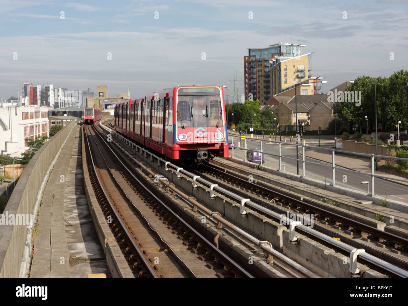 One DLR train leaving and one arriving at the West Silvertown Station in east London`s docklands. - Stock Image
