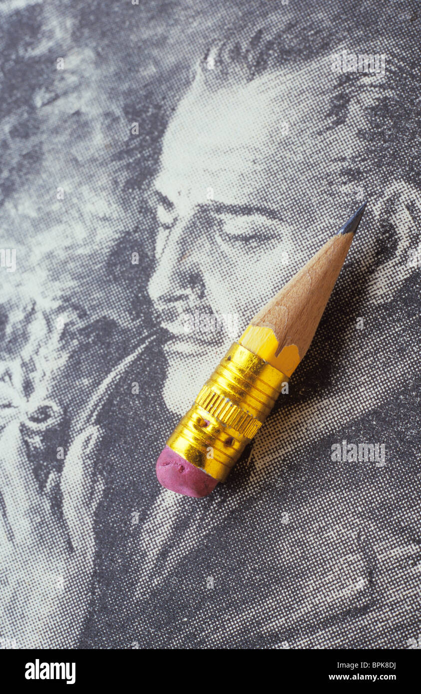 Sharpened pencil stub with eraser attached lying on newsprint drawing of 1930s man with moustache puffing on pipe - Stock Image
