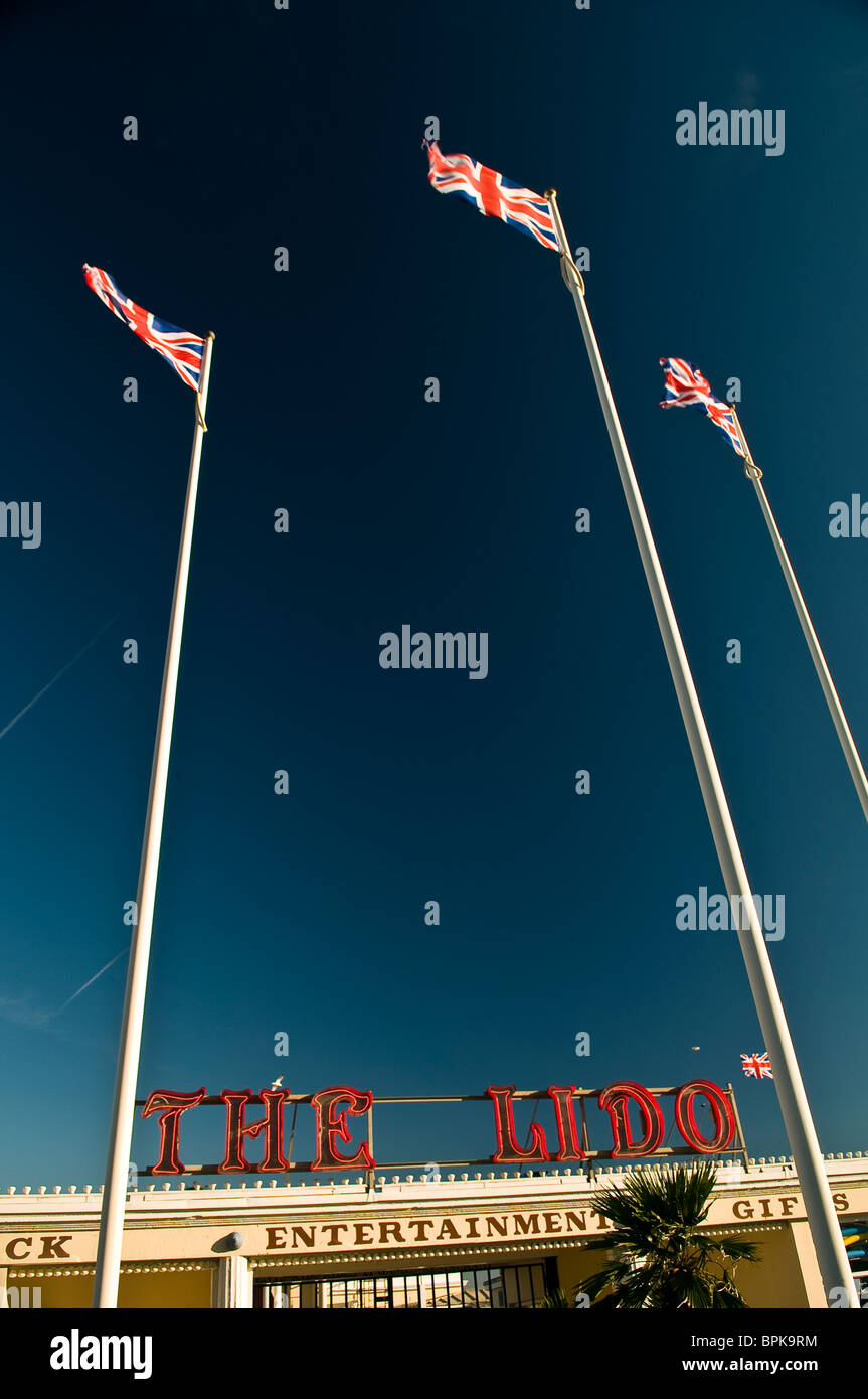 Three Union Jack flags fluttering in the breeze outside the Worthing Lido, West Sussex, UK - Stock Image
