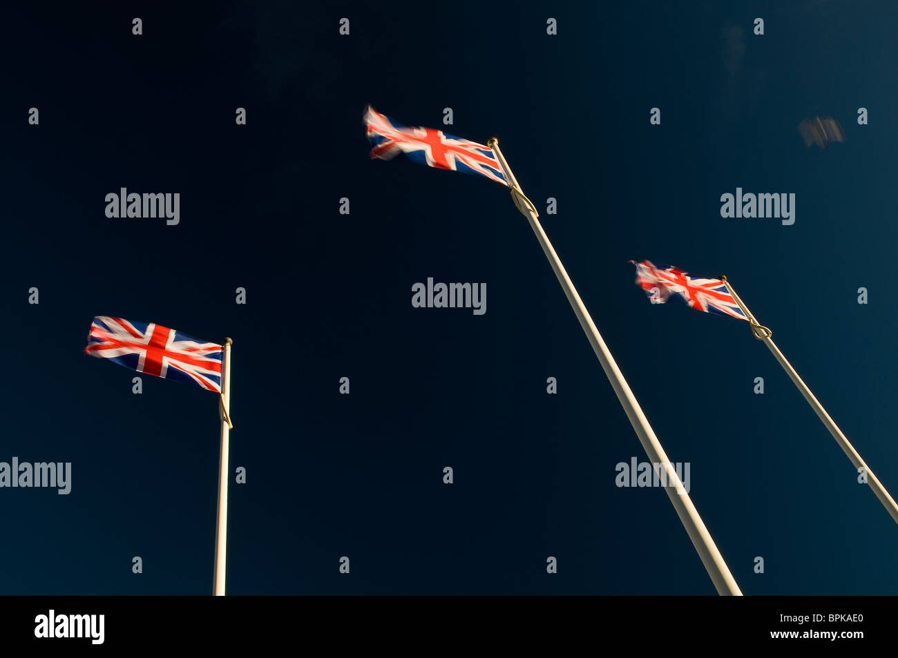 Three Union Jack flags fluttering in the breeze - Stock Image