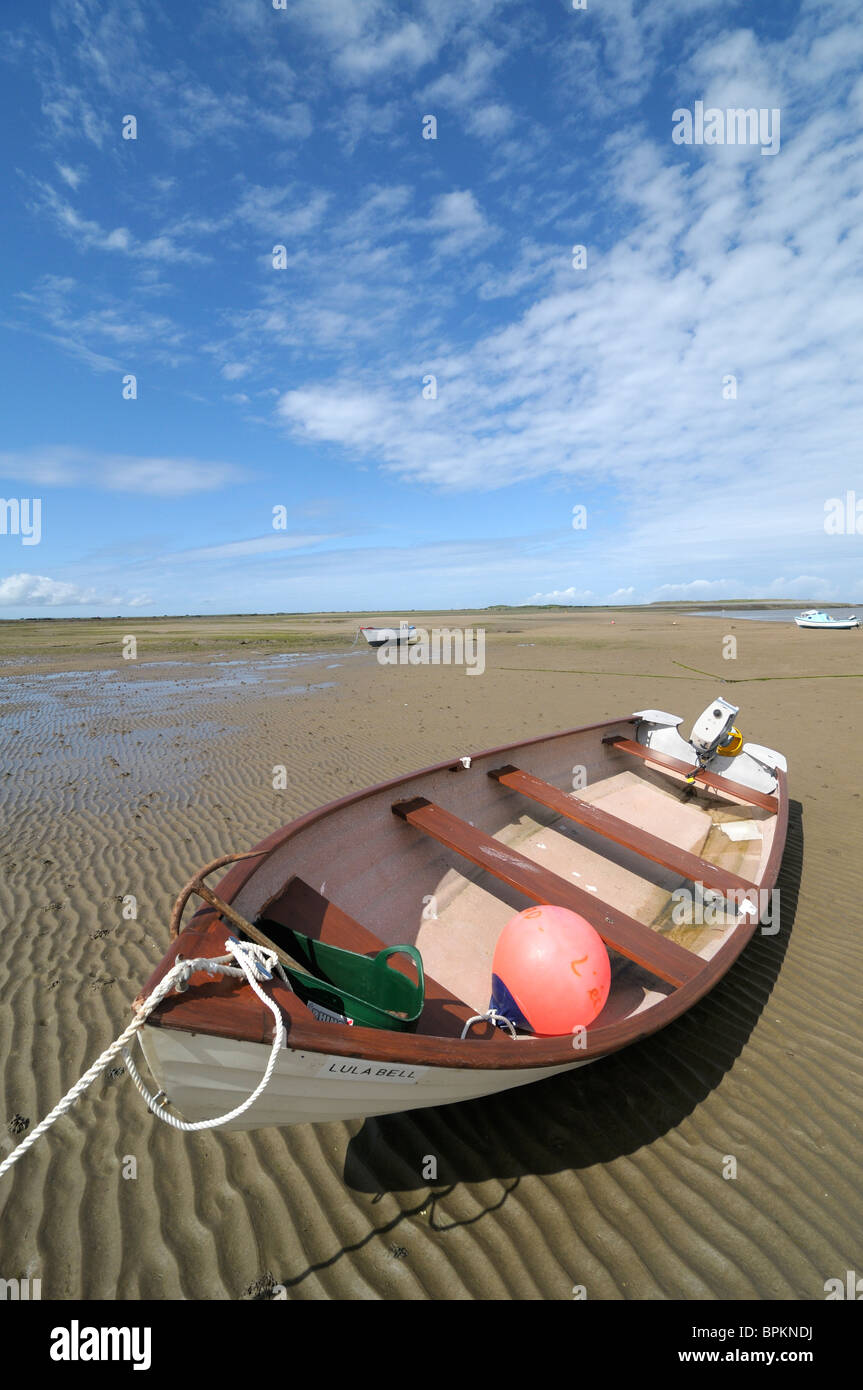 Beached open boat with outboard engine - Stock Image