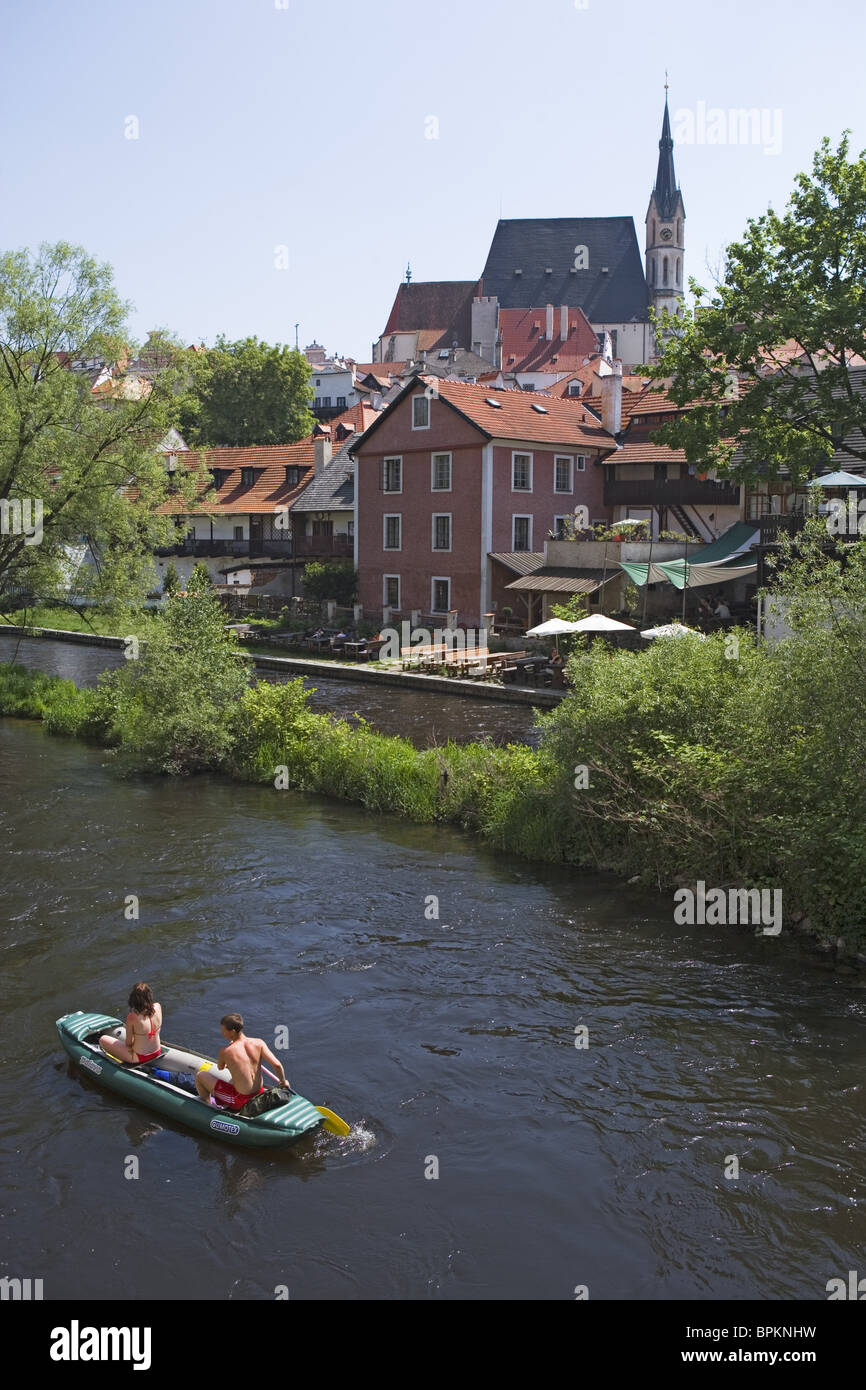 Canoeing on the Vltava river with the old town and the church of St. Veit in the back, Cesky Krumlov, South Bohemian - Stock Image